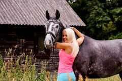 Beautiful blonde woman and her horse in rural area Stock Photo