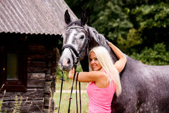 Beautiful blonde woman and her horse in rural area Royalty Free Stock Photo