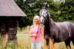 Beautiful blonde woman and her horse in rural area Royalty Free Stock Image