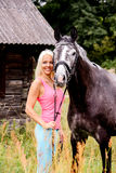 Beautiful blonde woman and her horse in rural area Stock Photography