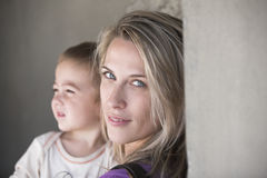 Beautiful blonde woman and her little son together. Blue eyes, blonde, long hair, beautiful young mother holds her baby, and smiles Royalty Free Stock Image