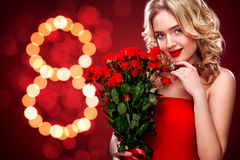 Beautiful blonde woman holding bouquet of red roses on bokeh background. International Women`s Day, Eight March Stock Images