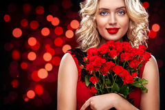 Beautiful blonde woman holding bouquet of red roses on bokeh background. International Women`s Day, Eight March Royalty Free Stock Image