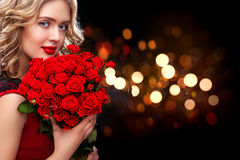 Beautiful blonde woman holding bouquet of red roses on bokeh background. Saint Valentine and International Women`s Day Royalty Free Stock Image
