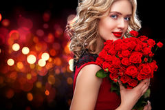Beautiful blonde woman holding bouquet of red roses on bokeh background. Saint Valentine and International Women`s Day Stock Photos