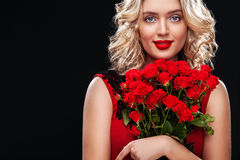 Beautiful blonde woman holding bouquet of red roses. International Women`s Day, Eight March celebration. Royalty Free Stock Image