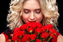 Beautiful blonde woman holding bouquet of red roses. International Women`s Day, Eight March celebration. Royalty Free Stock Photo