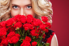 Beautiful blonde woman holding bouquet of red roses. Saint Valentine and International Women`s Day, Eight March Royalty Free Stock Photos
