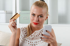 Beautiful blonde woman holding golden credit Stock Image