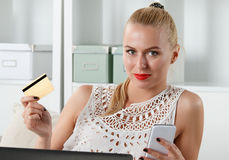 Beautiful blonde woman holding golden credit Stock Images