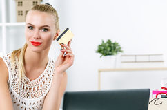 Beautiful blonde woman holding golden credit card. And looking in camera. Young lady buying dresses and new stuff in house via internet. Shopping, consumerism Stock Photography
