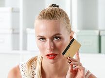 Beautiful blonde woman holding golden credit card Stock Photos