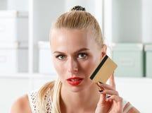 Beautiful blonde woman holding golden credit card Stock Photos