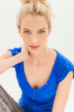 Beautiful blonde woman holding hand behind neck and smiles Royalty Free Stock Images