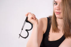 Beautiful blonde woman holding handcuffs. Royalty Free Stock Images