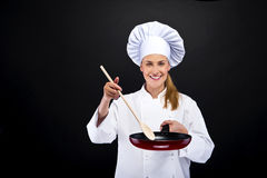 Beautiful blonde woman holding pan on white dark backg Stock Photo