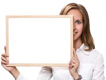 Beautiful blonde woman holding a white chalkboard. Royalty Free Stock Photos