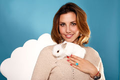 Beautiful blonde woman holding white fluffy little rabbits Royalty Free Stock Photo