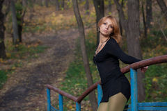 Beautiful blonde woman holds on to the railing footbridge. Beautiful blonde woman in a short black dress keeps for the railing of the bridge in autumn park Stock Images
