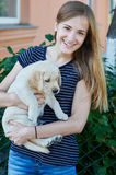 Beautiful blonde woman holds a white puppy Royalty Free Stock Images