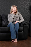 Beautiful blonde woman home sits on leather settee Royalty Free Stock Images