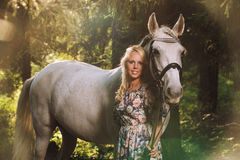 Beautiful blonde woman with a horse Royalty Free Stock Photos