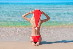 Beautiful Blonde Woman In Red Christmas Hat On Sea Beach. Royalty Free Stock Photography