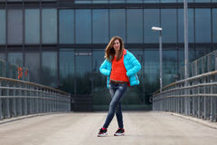 Beautiful blonde woman with jacket and orange sweater. Girl with long legs in blue jeans and sneakers standing on a bridge royalty free stock photos