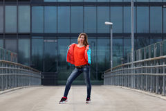 Beautiful blonde woman with jacket and orange sweater. Girl with long legs in blue jeans and sneakers standing on a bridge royalty free stock images