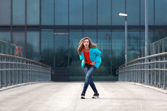 Beautiful blonde woman with jacket and orange sweater. Girl with long legs in blue jeans and sneakers standing on a bridge royalty free stock image