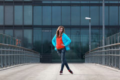 Beautiful blonde woman with jacket and orange sweater. Girl with long legs in blue jeans and sneakers standing on a bridge Stock Image