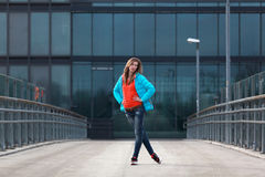 Beautiful blonde woman with jacket and orange sweater. Girl with long legs in blue jeans and sneakers standing on a bridge Stock Photography