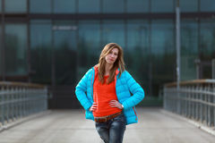 Beautiful blonde woman with jacket and orange sweater. Girl with long legs in blue jeans and sneakers standing on a bridge Royalty Free Stock Photography