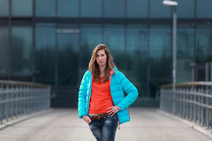 Beautiful blonde woman with jacket and orange sweater. Girl with long legs in blue jeans and sneakers standing on a bridge royalty free stock photo