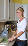 Beautiful blonde woman in kitchen Royalty Free Stock Image