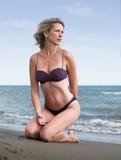 Beautiful blonde woman kneels at the sandy beach. Sexy woman in purple bikini at the sunny, sandy beach Royalty Free Stock Photo