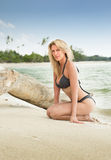 Beautiful blonde woman kneels on sandy tropical beach Royalty Free Stock Photo