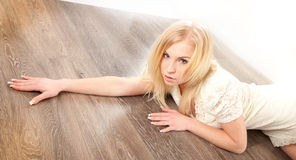 Beautiful blonde woman laying on the floor Royalty Free Stock Photography