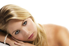 Beautiful blonde woman laying her head on a table Royalty Free Stock Photos