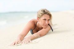 Beautiful, blonde woman lays on sandy beach Royalty Free Stock Images