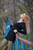 Beautiful blonde woman leaned on the railing of footbridge Stock Images