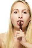 Beautiful blonde woman licking on her chocolate co. Vered finger on white background Stock Photo