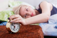 a beautiful blonde woman lies on the bed with her eyes open and stops the alarm clock with her hand stock photo