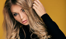 Beautiful blonde woman with long curly hair. Stock Photography