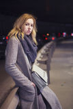Beautiful blonde woman in long grey warm coat, skirt, boots and Royalty Free Stock Photography