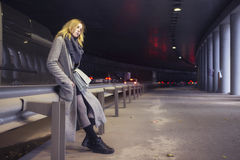 Beautiful blonde woman in long grey warm coat, skirt, boots and Stock Image