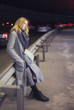 Beautiful blonde woman in long grey warm coat, skirt, boots and Stock Photography