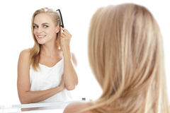 Beautiful blonde woman with long hair tidy up her hair using hai Stock Photo