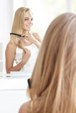 Beautiful blonde woman with long hair tidy up her hair using hai Stock Image
