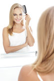 Beautiful blonde woman with long hair tidy up her hair using hai Royalty Free Stock Images